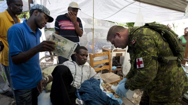 Petty Officer Paul Spracklin is watched as he tends to a man with a foot injury at the hospital in Jacmel, Haiti Monday Janaury 18, 2010. (THE CANADIAN PRESS/Adrian Wyld)