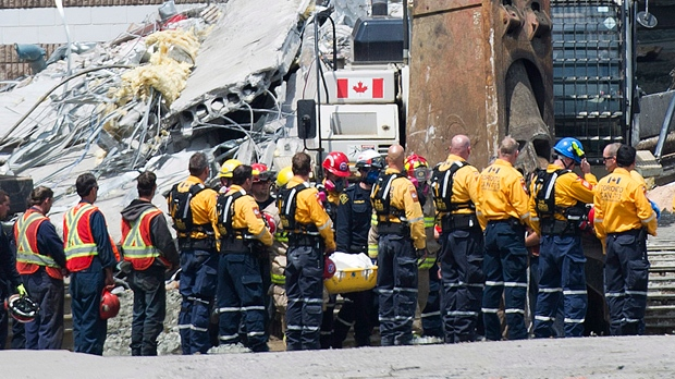 Rescue workers remove their hard hats as firefighters carry a second body out of the Algo Centre Mall in Elliot Lake, Ont., on Wednesday, June 27, 2012. (The Canadian Press/Nathan Denette)