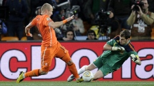 Spain goalkeeper Iker Casillas, right, blocks Netherlands' Arjen Robben from scoring during the World Cup final soccer match between the Netherlands and Spain at Soccer City in Johannesburg, South Africa, Sunday, July 11, 2010. (AP Photo / Martin Meissner)
