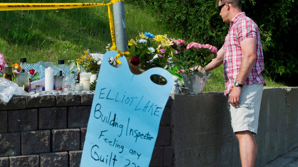 A man lays flowers at a memorial site the day after the recovery of two bodies at the Algo Centre Mall in Elliot Lake, Ont., on Thursday, June 28, 2012, following collapse of the mall's roof last Saturday. (Nathan Denette / THE CANADIAN PRESS)