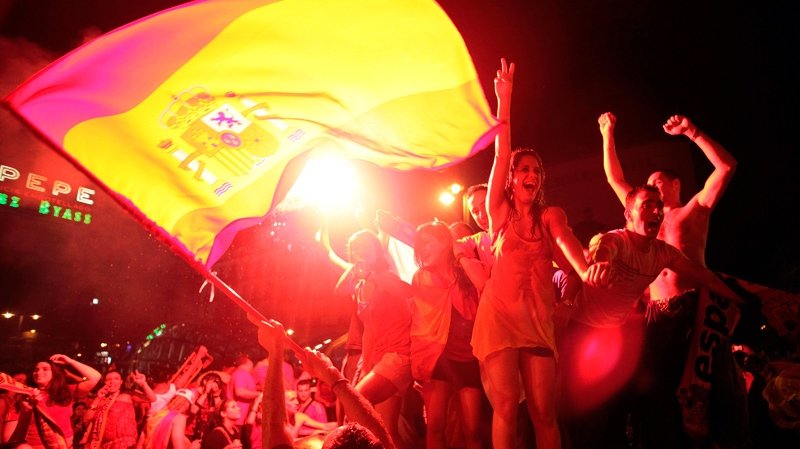 Under the light of flares, Spanish fans celebrate in a fountain in downtown Madrid after Spain defeated the Netherlands to win the World Cup soccer final, which is being played in South Africa, on Sunday, July 11, 2010. (AP / Arturo Rodriguez)