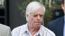 Escorted by police, financial adviser Earl Jones leaves an office tower in Montreal, Monday, July 27, 2009. (THE CANADIAN PRESS/Graham Hughes)