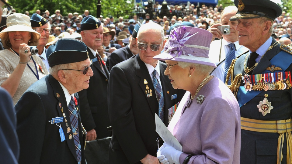 Queen Elizabeth II and Prince Philip, right, talk to Ed Carter-Edwards, left, a former member of Bomber Command from Canada, after unveiling the Bomber Command Memorial in Green Park, Thursday, June 28, 2012. (AP / John Stillwell)