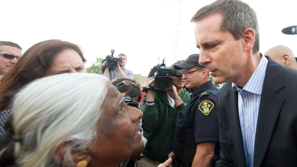 Ontario Premier Dalton McGuinty, right, greets people of the community after speaking at a press conference regarding the rescue and recovery of two bodies at the Algo Centre Mall in Elliot Lake, Ont., on Wednesday, June 27, 2012. (Nathan Denette / THE CANADIAN PRESS)
