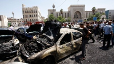 Syrians inspect burned cars