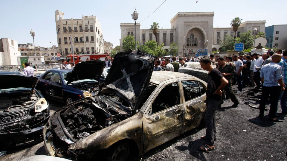 Syrians inspect burned cars at the site of a blast in the Syrian capital Damascus Thursday June 28, 2012. (AP / Muzaffar Salman)