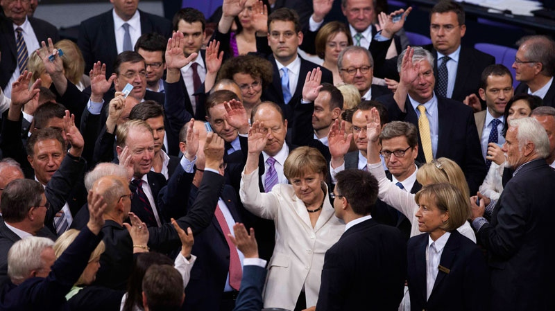 FILE - German Chancellor Angela Merkel, center, raises her hand with other lawmakers during a voting about the EU's fiscal compact at the parliament Bundestag in Berlin, Friday, June 29, 2012. (AP / Markus Schreiber)