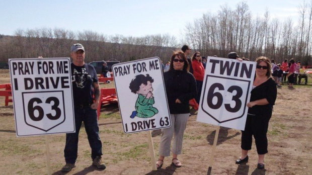 Protesters hold signs at a rally in Fort McMurray, Alta. on May 5, 2012.