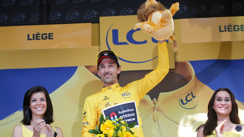 Fabian Cancellara of Switzerland, wearing the overall leader's yellow jersey, celebrates on the podium after winning the prologue of the Tour de France cycling race in Liege, Belgium, Saturday June 30, 2012. (AP / Christophe Ena)