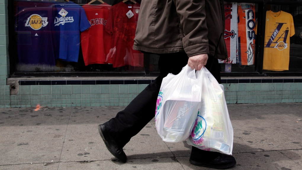 Man walks along the street with plastic bags