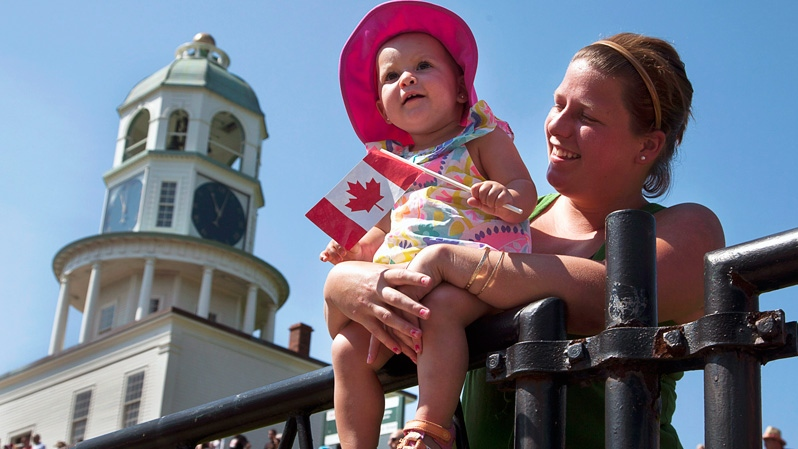 One-year-old Audrey Lamey and her mom Brittany Osmaond watch the Canada Day parade in Halifax on Sunday, July 1, 2012. (Andrew Vaughan / THE CANADIAN PRESS)