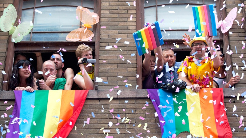 Spectators wave and throw confetti during the Gay Pride Parade below them in Toronto, July, 1, 2012. (Michelle Siu / THE CANADIAN PRESS)
