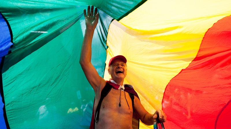 A participant stands beneath a rainbow flag during the Gay Pride Parade in Toronto, July, 1, 2012. (Michelle Siu / THE CANADIAN PRESS)
