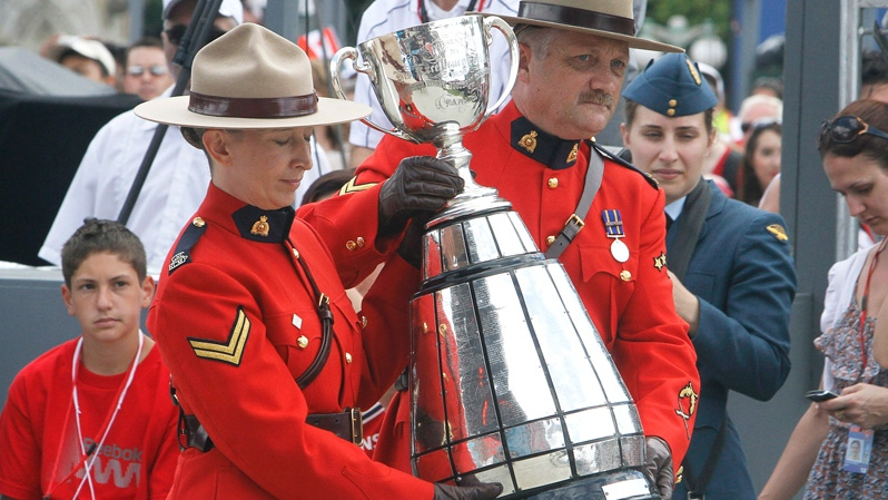 Two RCMP constables carry the Grey Cup, celebrating Canada Day on Parliament Hill in Ottawa, Sunday July 1, 2012. (Fred Chartrand / THE CANADIAN PRESS)