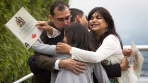 Adrian Pernalete, left, and his wife Virginia Pernalete, right, embrace their children Andrea, bottom centre, 10, and Adrian, 13, as they leave the stage after being sworn in as Canadian citizens during a special Canada Day citizenship ceremony for 60 people in Vancouver, B.C., on Sunday July 1, 2012. (Darryl Dyck / THE CANADIAN PRESS)