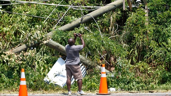 Joe Tiago takes pictures of a downed utility pole and electric transformer in Springfield, Virginia, Sunday, July 1, 2012. (AP / Pablo Martinez Monsivais)