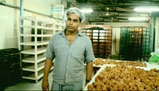 An inmate, who is serving life for murder in Tihar Jail, is seen standing next to baked goods.