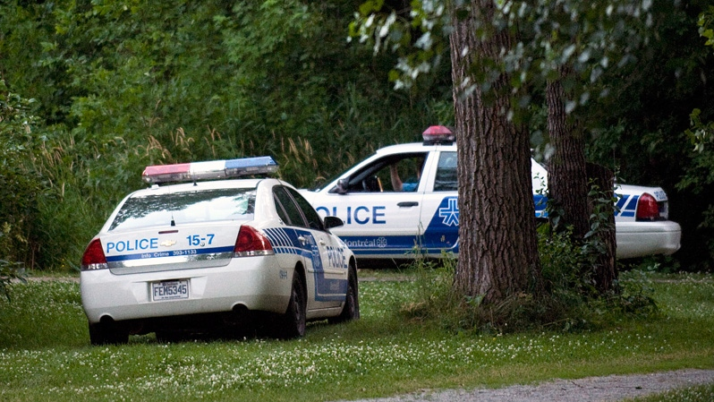 Police vehicles are shown at a Montreal park where they carried out a search on Sunday, July 1, 2012. (Graham Hughes / THE CANADIAN PRESS)