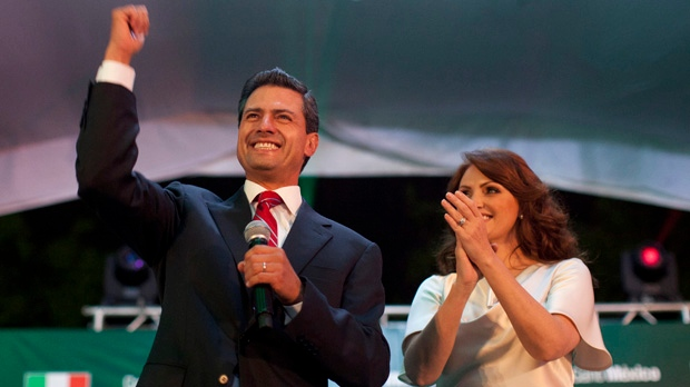 Enrique Pena Nieto, presidential candidate for the Revolutionary Institutional Party (PRI), left, speaks to supporters with his wife Angelica Rivera at the party's headquarters in Mexico City early Monday, July 2, 2012. (AP Photo/Alexandre Meneghini)
