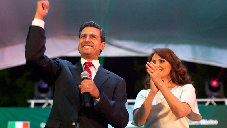 Enrique Pena Nieto, presidential candidate for the Revolutionary Institutional Party (PRI), left, speaks to supporters accompanied by his wife Angelica Rivera at the party's headquarters in Mexico City, early Monday, July 2, 2012. (AP / Alexandre Meneghini)