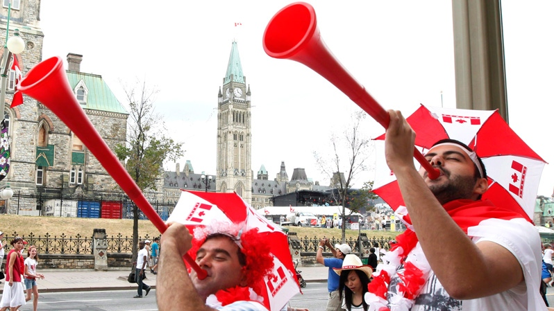 Ersel Ture and Euce Igoz blow horns as they celebrate Canada Day near Parliament Hill in Ottawa, Sunday, July 1, 2012. (Fred Chartrand / THE CANADIAN PRESS)