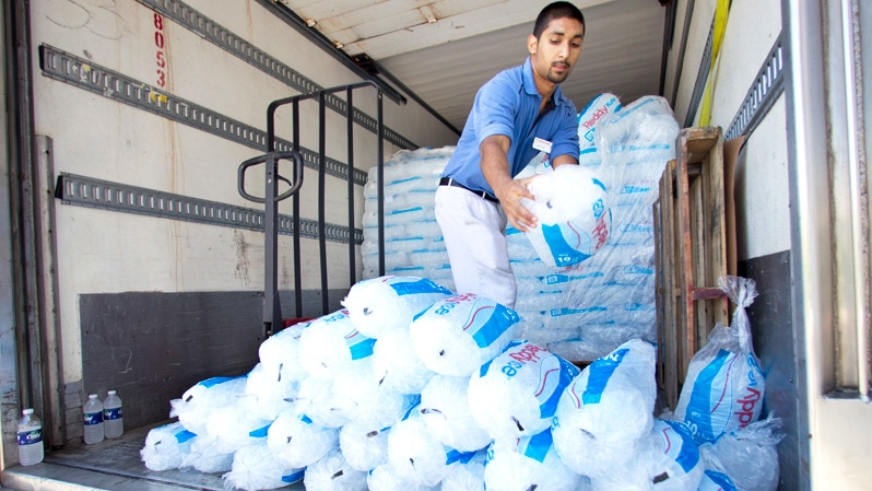 Harris Teeter grocery store employee Andrew Singh piles bags of ice for free distribution in Bethesda, Md., Monday, July 2, 2012. (AP / Manuel Balce Ceneta)