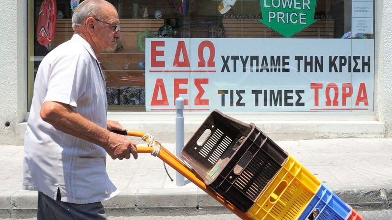 A man pushes a trolley as he walks past a storefront in southern port city of Limassol, Cyprus, Thursday, June 28, 2012. (AP / Pavlos Vrionides)