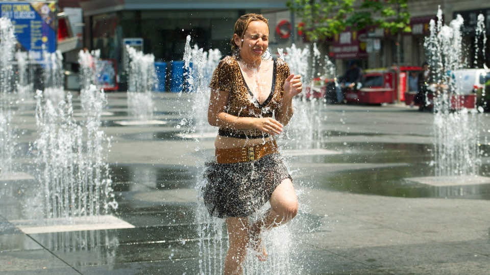 A woman cools down in the water sprinklers at Dundas Square as she take in the extreme heat in Toronto on Tuesday, June 19, 2012. (Nathan Denette / THE CANADIAN PRESS)