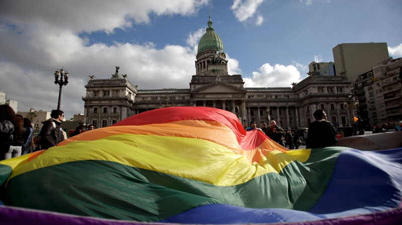 Demonstrators wave a gay pride flag outside Congress in support of a proposal to legalize same-sex marriage in Buenos Aires, Wednesday July 14, 2010. (AP Photo/Natacha Pisarenko)