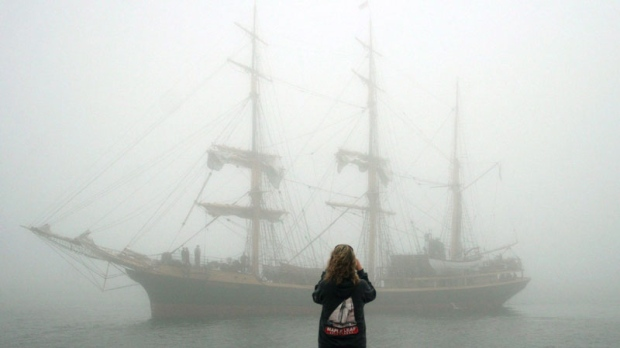 Torunn Andersen takes a photo of the Picton Castle as it rolls in through the fog for the Tall Ships Nova Scotia Festival in Halifax, Nova Scotia on Thursday, July 12, 2007. (CP PHOTO/Ryan Taplin)