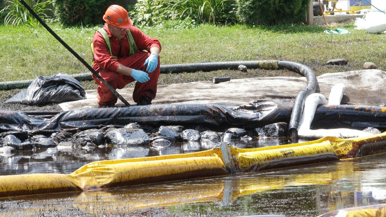 A worker monitors water in Talmadge Creek in Marshall Township, Mich., near the Kalamazoo River as oil from a ruptured pipeline, owned by Enbridge Inc., is attempted to be trapped by booms, July 29, 2010. (AP / Paul Sancya)