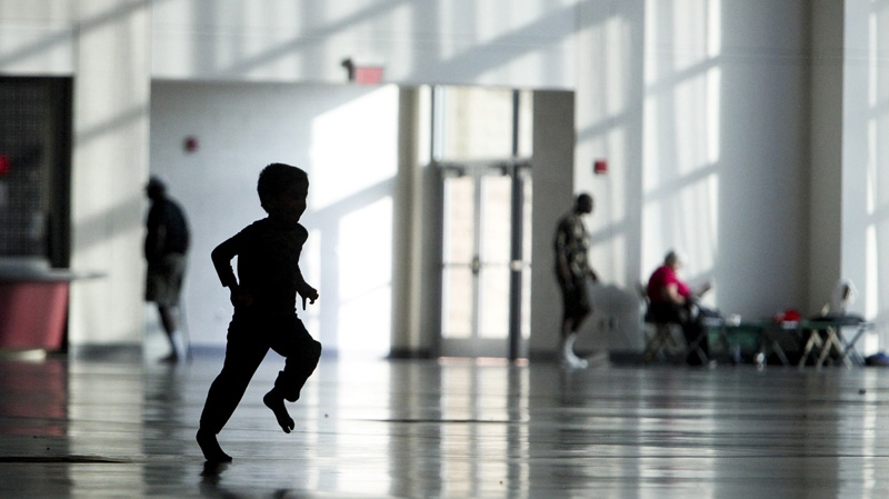 A child runs through a Red Cross overnight shelter at the Roanoke Civic Center Special Events Center in Roanoke, Va. on Monday, July 2, 2012. (The Roanoke Times, Kyle Green)