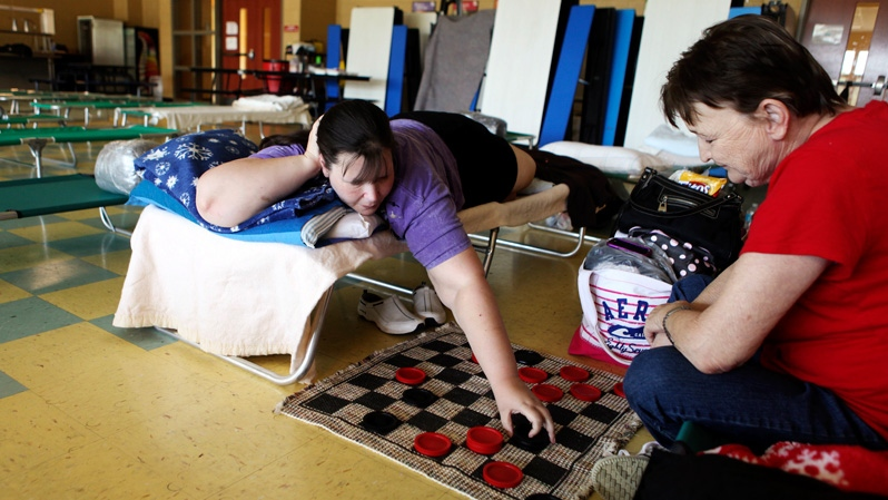 Denise Garvey and her mother Donna Alley play checkers at a cooling center set up in a cafeteria in Craig County, Va., Monday, July 2, 2012. (The Roanoke Times / Jeanna Duerscherl)