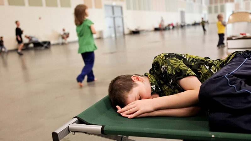 Andrew Tillman, 12, sleeps on a cot in a Red Cross overnight shelter at the Roanoke Civic Center Special Events Center in Roanoke, Va., on Monday, July 2, 2012. (The Roanoke Times / Kyle Green)