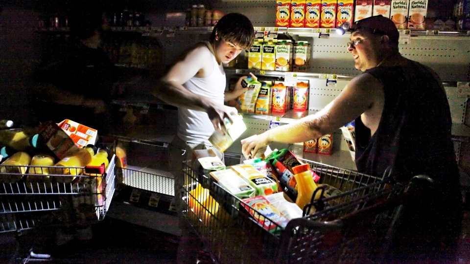 David Robertson and Steve Jones fill their shopping cart with juice at the Mick-or-Mack IGA grocery store in New Castle, Va., Monday, July 2, 2012.  (AP / The Roanoke Times, Jeanna Duerscherl)