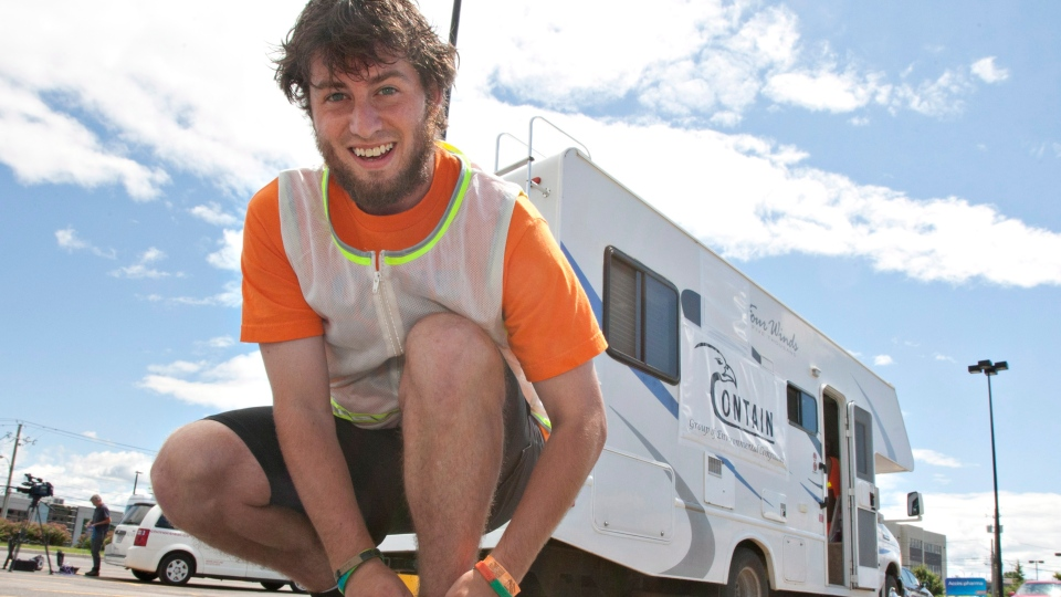 Curtis Hargrove ties on his running shoes behind his camper at a Saint-Romuald Que. shopping centre parking lot, Tuesday, July 3, 2012. (Jacques Boissinot / THE CANADIAN PRESS)