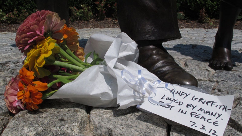 A bouquet of flowers sits at the foot of a statue of Andy Griffith at Pullen Park in Raleigh, N.C., on Tuesday, July 3, 2012. (AP / Allen Breed)