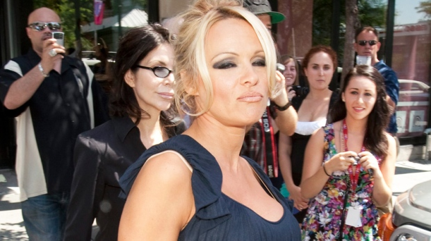 Pamela Anderson, who is performing at the Just for Laughs comedy festival, leaves after holding a news conference in Montreal, Thursday, July 15, 2010. (Ryan Remiorz / THE CANADIAN PRESS)