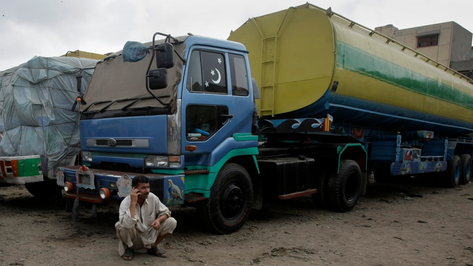 A Pakistani driver talks on his cell phone as he sit next to oil tankers, which were used to transport NATO oil supplies to Afghanistan, parked at a terminal in Karachi, Pakistan, Wednesday, July 4, 2012. (AP / Fareed Khan)