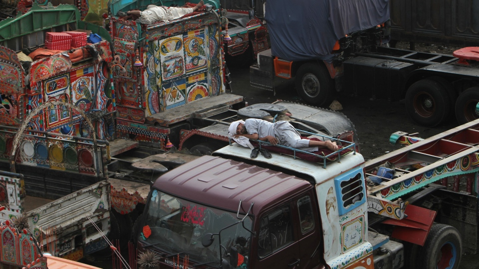 Pakistani drivers sleep atop of trucks, which were used to transport NATO supplies to Afghanistan, parked at a terminal in Karachi, Pakistan, Wednesday, July 4, 2012. (AP / Fareed Khan)