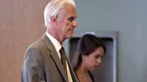 Former Quebec judge Jacques Delisle, left, walks into court with his granddaughter Anne Sophie Morency, Thursday, June 14, 2012 in Quebec City. (The Canadian Press/Jacques Boissinot)