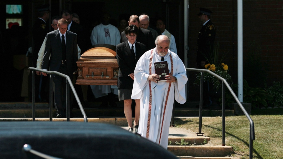 A casket carrying the remains of 74-year-old Doloris Perizzolo leaves the Our Lady of Fatima Parish in Elliot Lake, Ont., on Wednesday, July 4, 2012. (Kenneth Armstrong / THE CANADIAN PRESS)