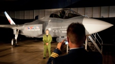 A Canadian Forces pilot has his picture taken in front of a F-35 Strike Fighter prior to an announcement in Ottawa, Friday July 16, 2010.  (Adrian Wyld / THE CANADIAN PRESS)