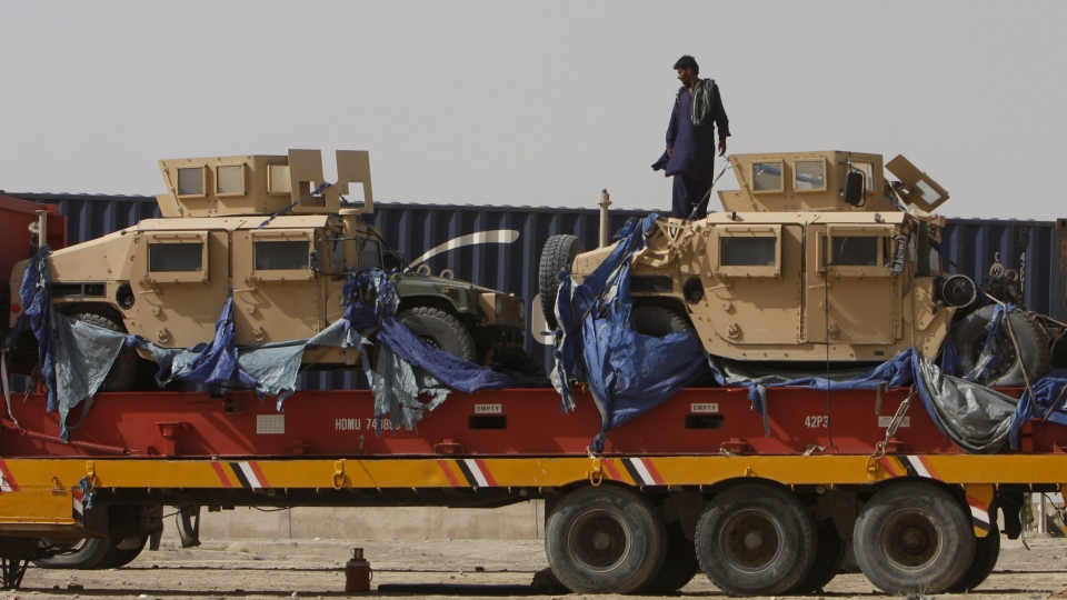 A driver stands on top of a truck carrying NATO Humvees at a terminal in the Pakistani-Afghan border, in Chaman, Pakistan, Wednesday, July 4, 2012. (AP / Matiullah Achakzai)