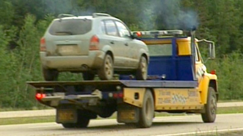 Lyle and Marie McCann's Hyundai Tucson is towed away after being discovered by police in an area west of Edmonton on Friday, July 16, 2010.
