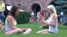 Two women sit on the lawn at Queen's Park during a demonstration on Saturday, July 17, 2010.