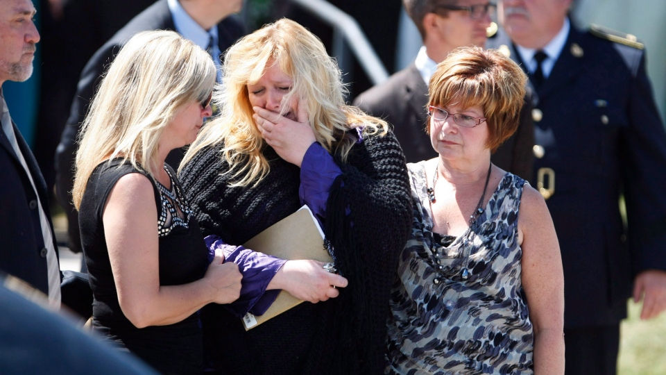 Mourners react outside the Our Lady of Fatima Parish after the funeral of 74-year-old Doloris Perizzolo in Elliot Lake, Ont., on Wednesday, July 4, 2012. (Kenneth Armstrong / THE CANADIAN PRESS)
