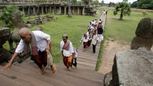 Visitors climb the steps of an ancient temple in Cambodia. The World Health Organization is probing a mystery disease that's killed 61 children in the country. (AP / Heng Sinith)