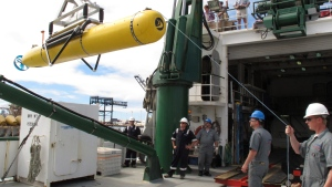Crew members lift an autonomous underwater vehicle from a ship to dockside waters in Honolulu on Sunday, July 1, 2012. The unmanned mapping vehicle was used to find plane wreckage from Amelia Earhart's Lockheed Electra, which disappeared over the South Pacific 75 years ago. (AP/Oskar Garcia)