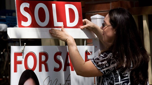"A real estate agent puts up a ""sold"" sign in front of a house in Toronto Tuesday, April 20, 2010. (The Canadian Press/Darren Calabrese)"